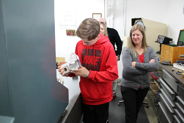 A McMinnville Middle School student holds a piece manufactured by a CNC machine. The students were told the piece would be landing on Mars.