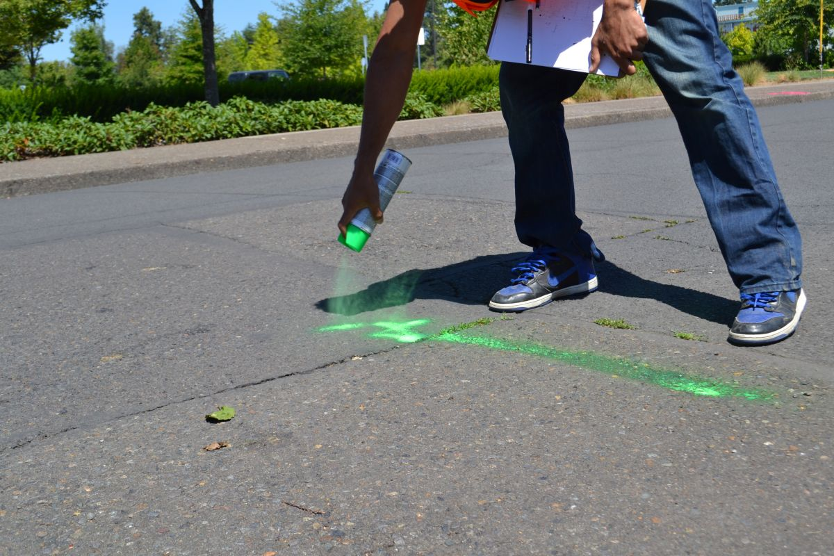 City of McMinnville Intern sprays markings on a road for his internship project