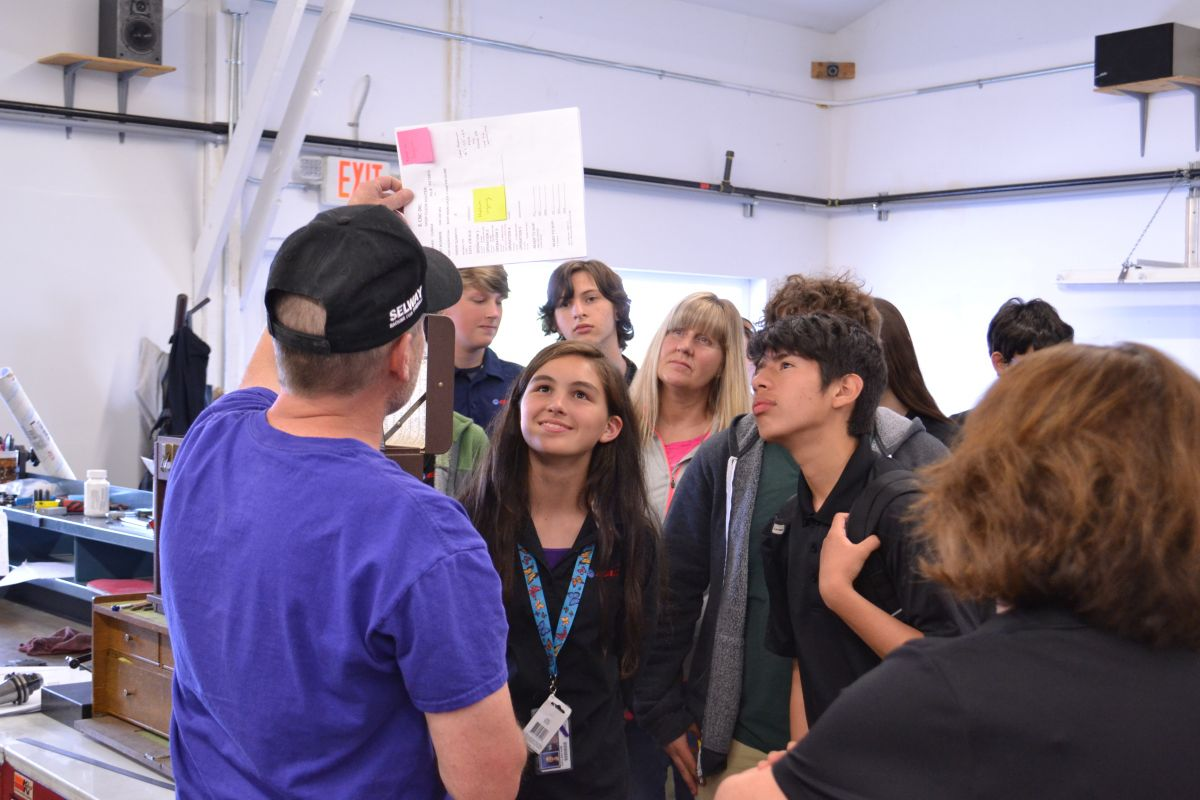 McMinnville High School students view plans for a piece being manufactured in the CNC machines