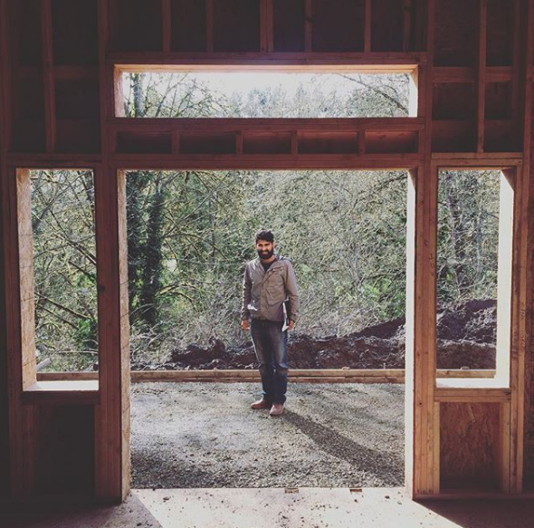 Abhi stands in the frame of his first official project, a house for a McMinnville resident.