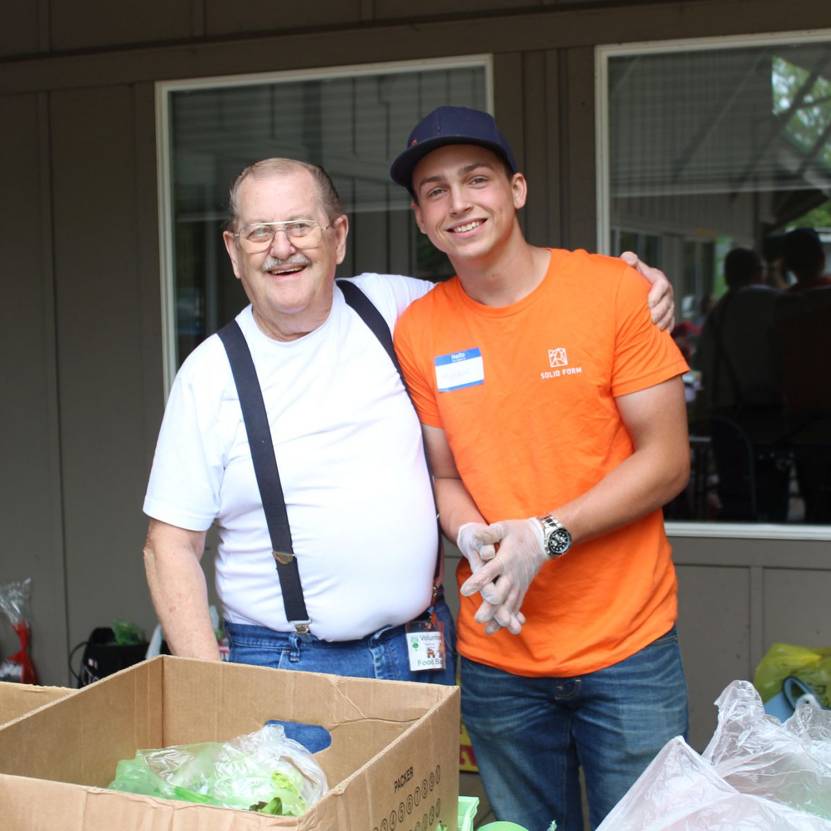 Marckus Smith, intern at Solid Form, stands with another volunteer at Harvest2Home