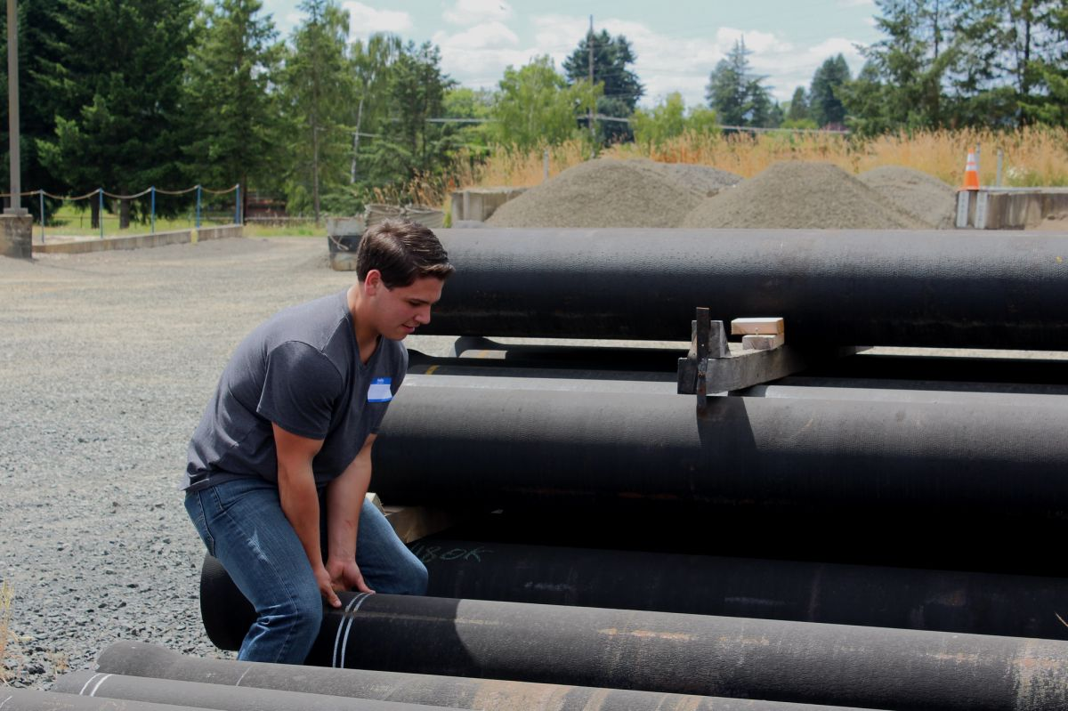 Kyle Cool, intern at Fackler Construction, lifts a water pipe for a large building project at McMinnville Water & Light
